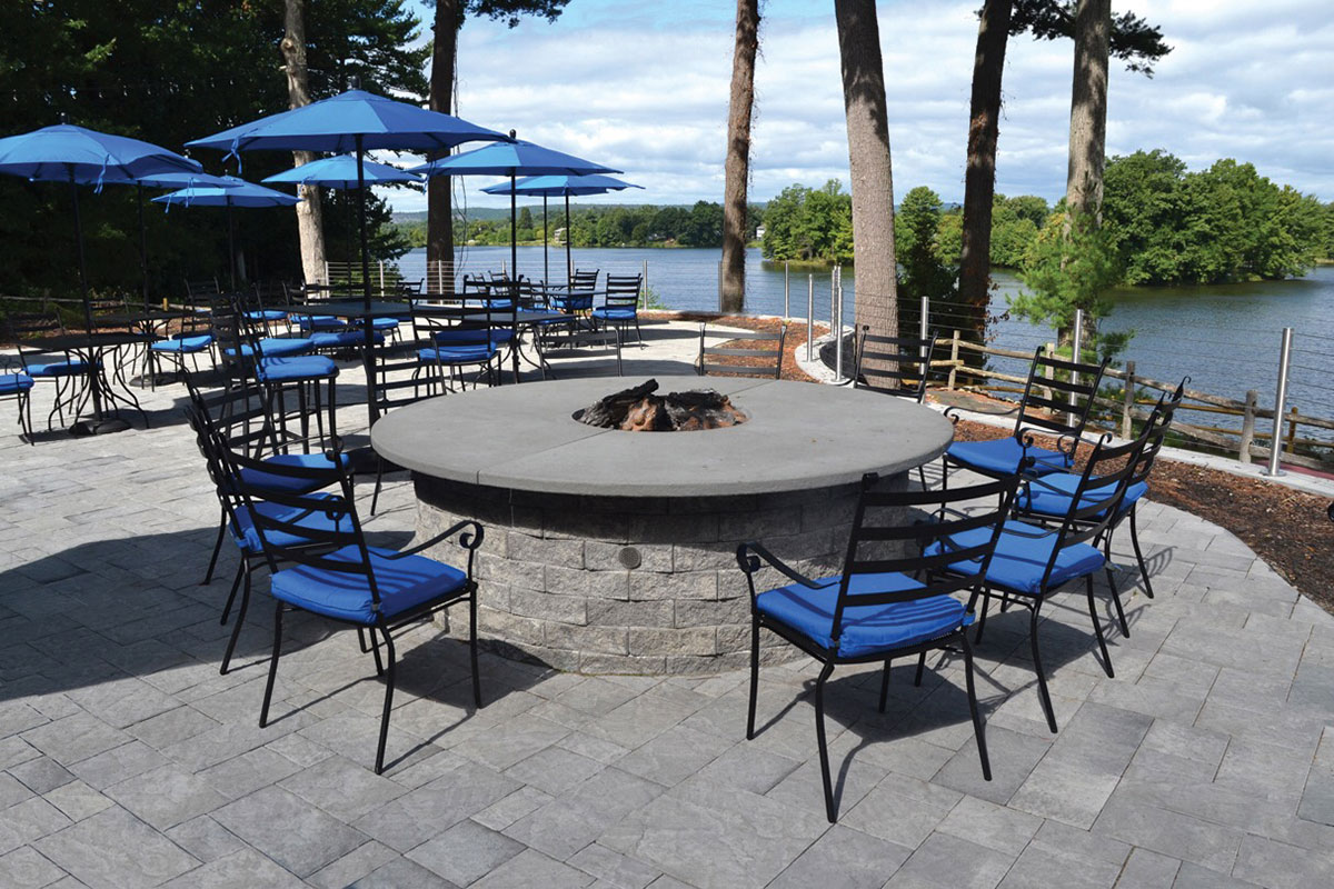 Stone patio with bonfire and chairs looking out onto the water