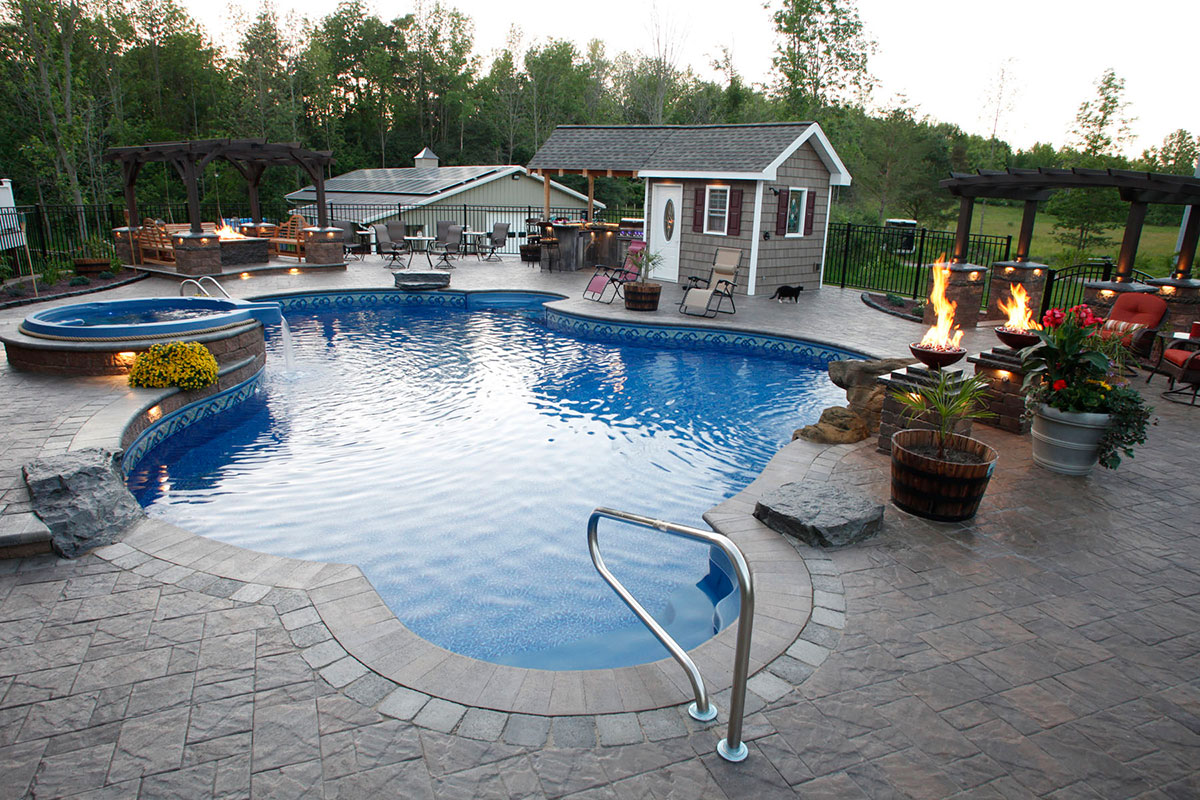 Stone patio with pool, hot tub, grilling are and bonfire