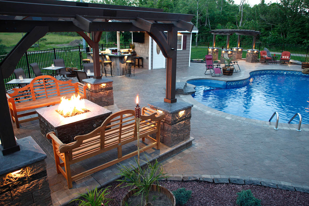 Stone patio with bonfire, pool, grilling area