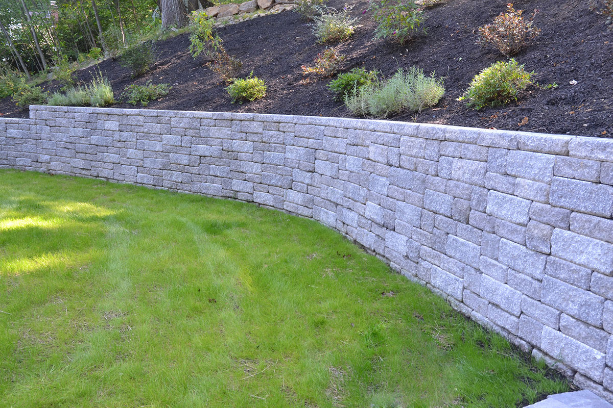 Stone wall separating grass and mulch