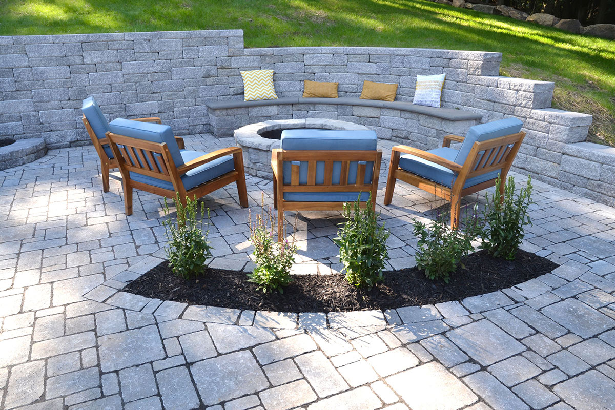 Stone bonfire area with retaining wall and chairs
