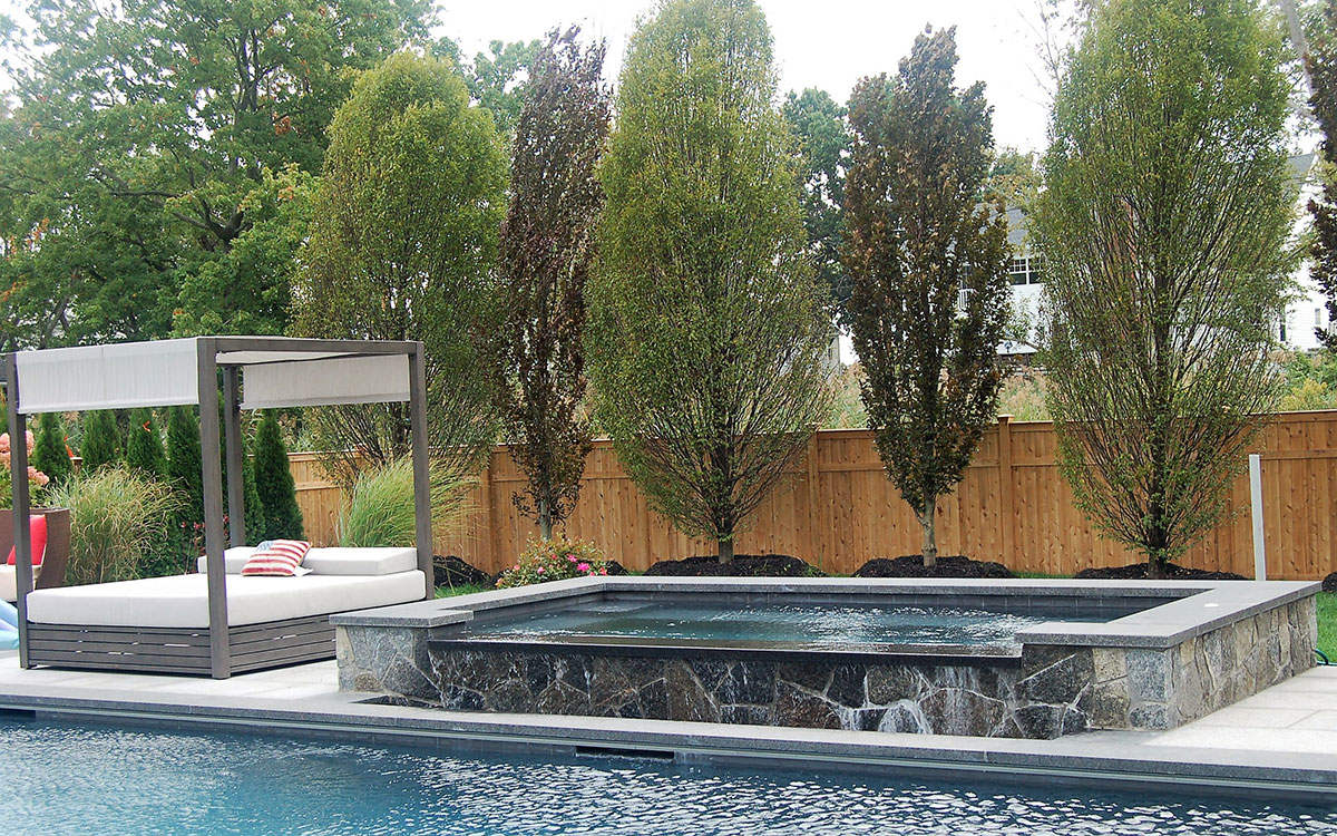 Stone pool and hot tub near daybed