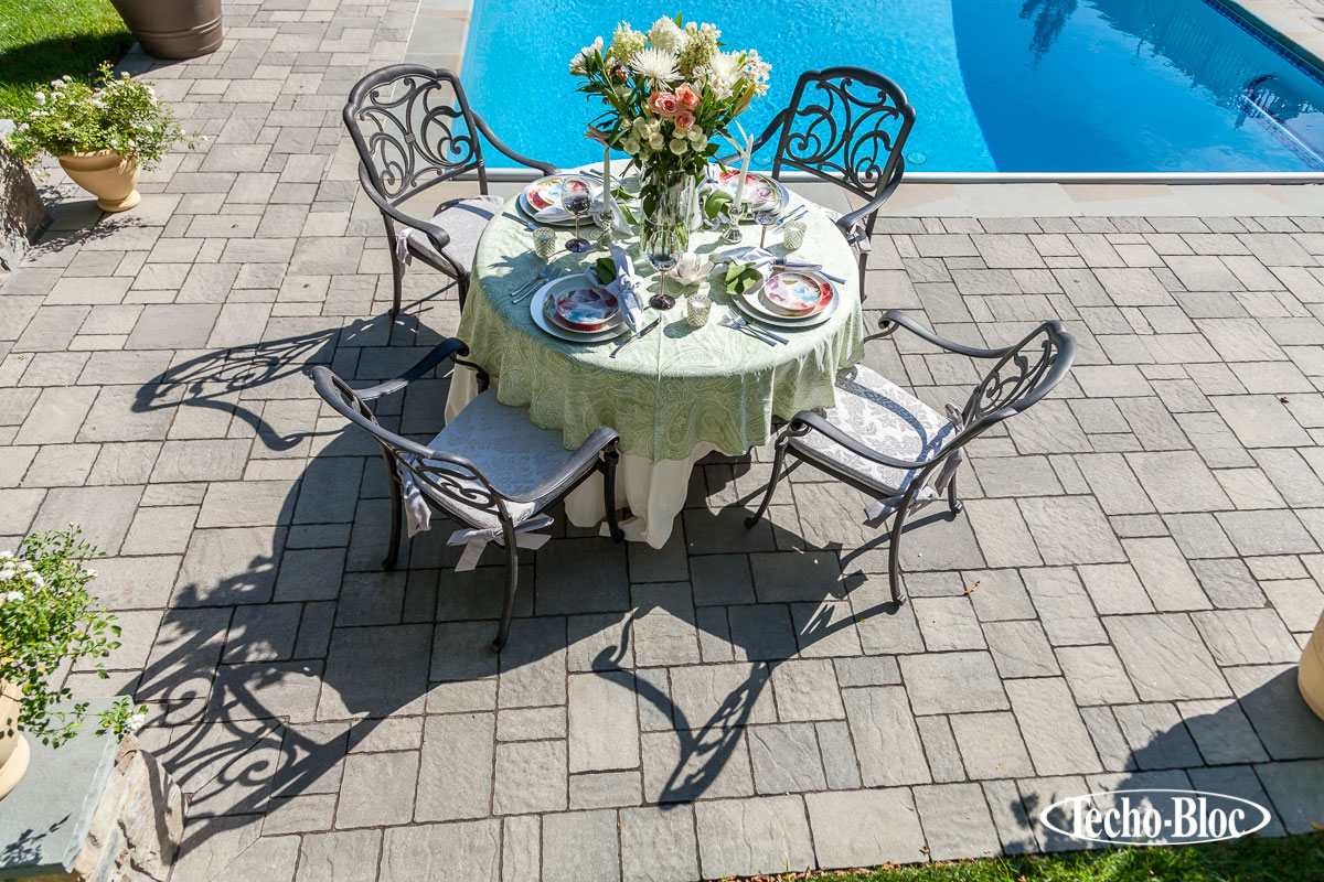 Stone patio and pool side with table and chairs