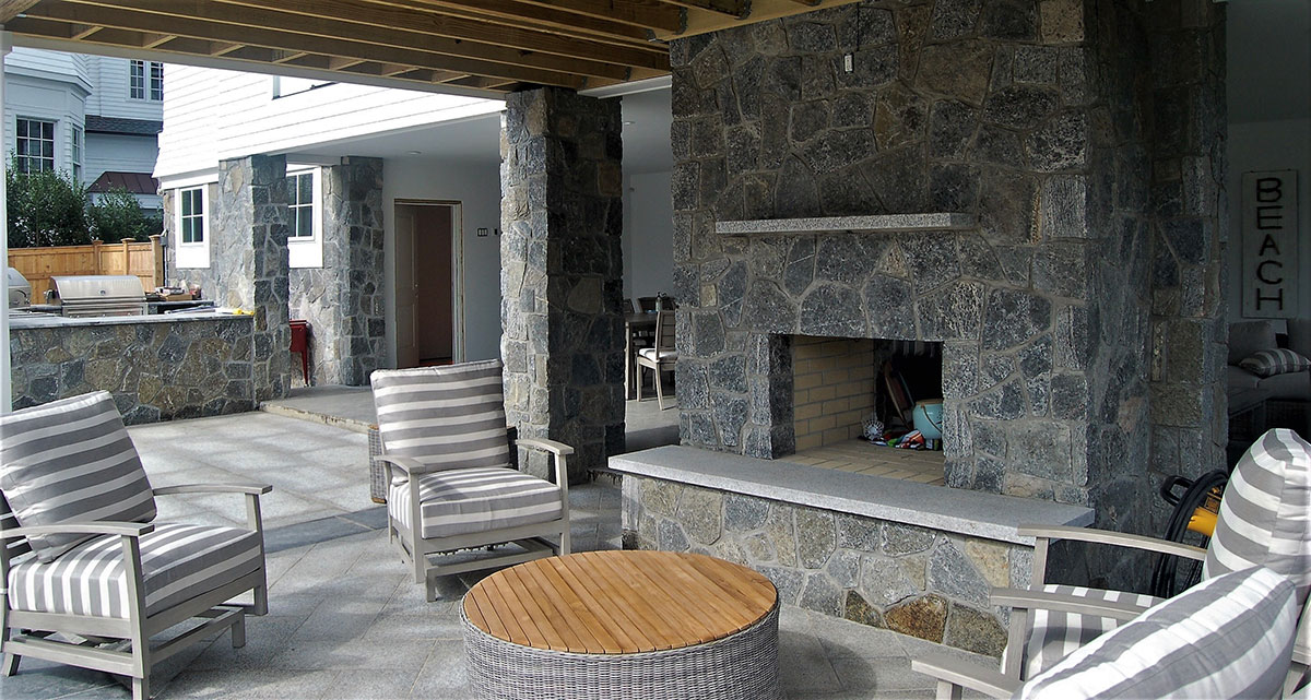 Stone patio with fireplace and grilling area